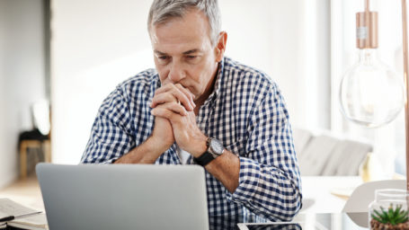 Older man sitting at laptop