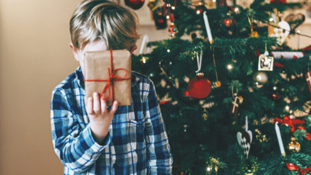 Boy holds up a present in front of his head.