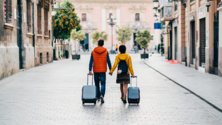 Young couple with suitcases.