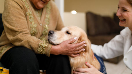 Senior woman and caregiver with therapy dog.