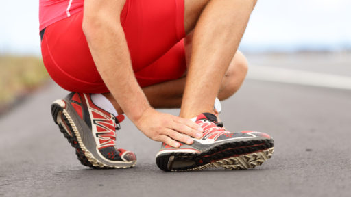Male runner touching foot in pain due to sprained ankle.