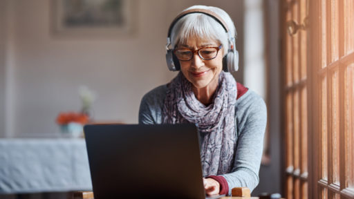 Shot of a senior woman using a laptop and headphones.