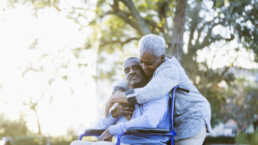 Portrait of a senior African American couple outdoors. The man is sitting in a wheelchair.