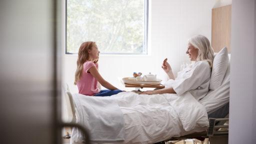 Granddaughter Visiting Grandmother In Hospital Bed For Afternoon Tea