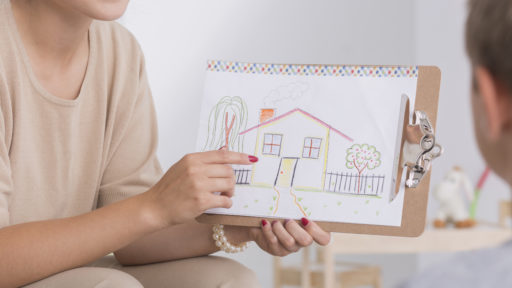 Image of smiling female therapist showing a drawing of house to a child