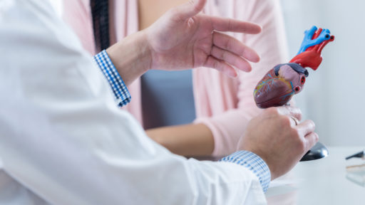 Image of a male cardiologist gesturing while discussing diagnosis with an unrecognizable female patient.