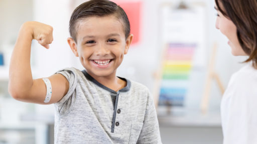 Image of an elementary age little boy sits in his unrecognizable pediatrician's office. He smiles for the camera as he flexes his arm muscles. There is a bandage on his arm. His pediatrician smiles at him.