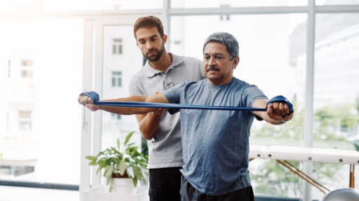 Image of a young male physiotherapist helping a mature male patient with movement exercises at a clinic.