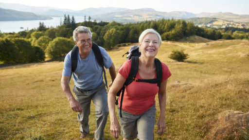 Senior Couple Climbing Hill On Hike Through Countryside