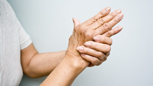 Elderly woman holding her arthritic hands