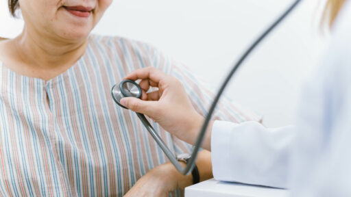 doctor using stethoscope to exam patient heart