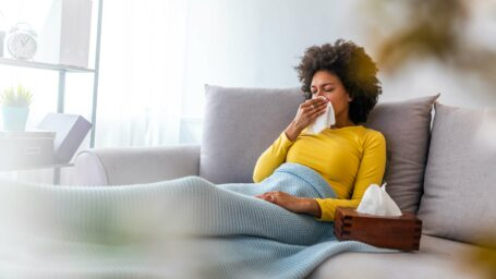 Sick young woman sitting on sofa blowing her nose at home in the sitting room. Photo of sneezing woman in paper tissue. Picture showing woman sneezing on tissue on couch in the living-room (Sick young woman sitting on sofa blowing her nose at home in