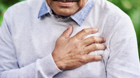Closeup shot of a mature man holding his chest in discomfort outdoors.