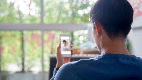 close up rear view of young man using smartphone to video conference to consulting about male hormone and physical with specialist and listen explaining at home for telemedicine health technology life concept